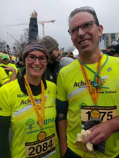 Tara P and Mike A at the end of the half marathon with medals
